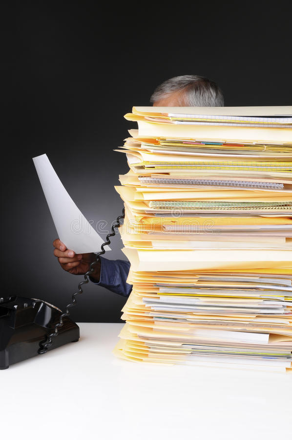 Businessman on Phone Behind Stack of Files