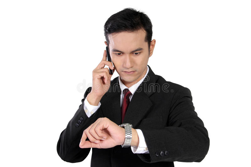 Businessman on phone checking the time, isolated on white royalty free stock images