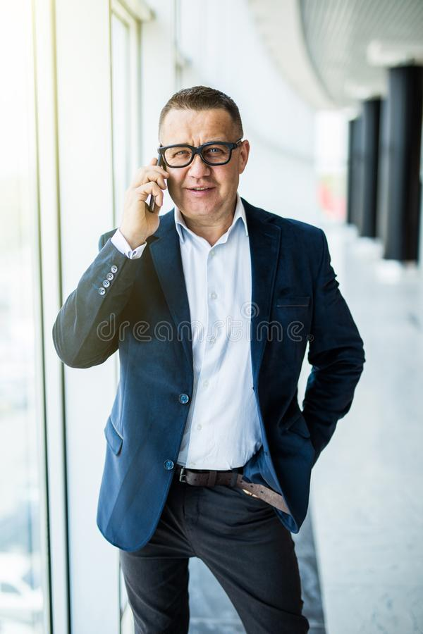 Businessman on the phone. Confident senior man in formalwear talking on the mobile phone and looking at camera in office royalty free stock photo