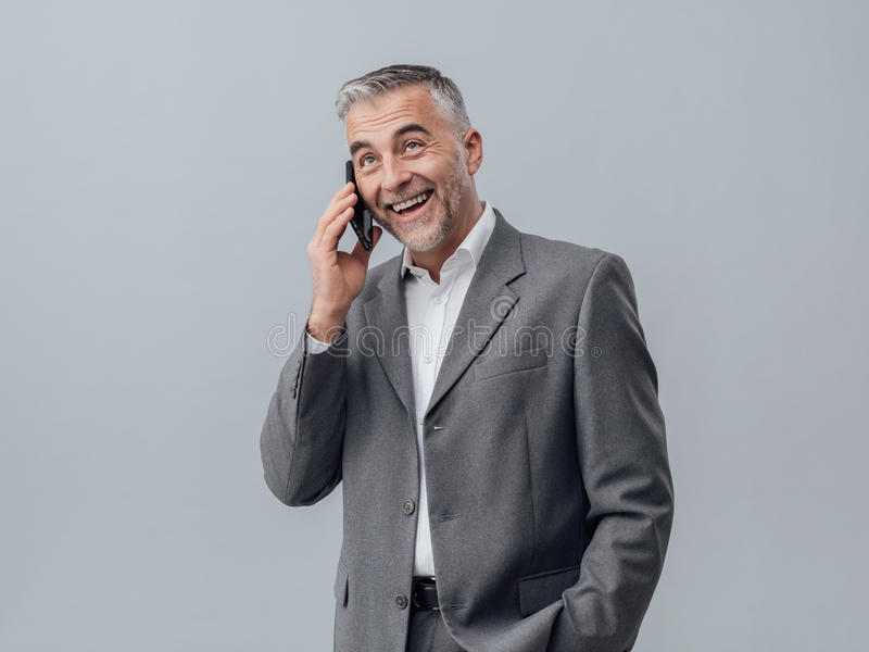 Businessman on the phone. Confident smiling businessman having a phone call with his smartphone royalty free stock images