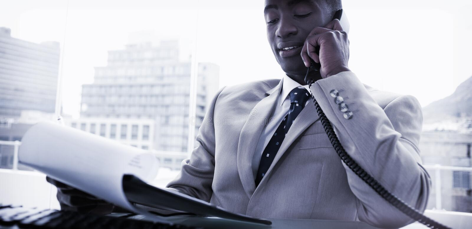 Businessman on the phone while reading a document royalty free stock photography