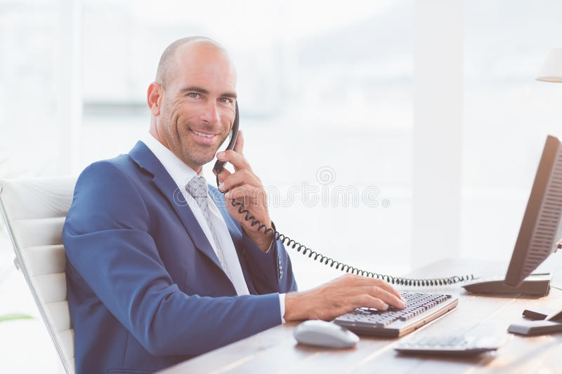 Businessman on the phone and using his computer stock image