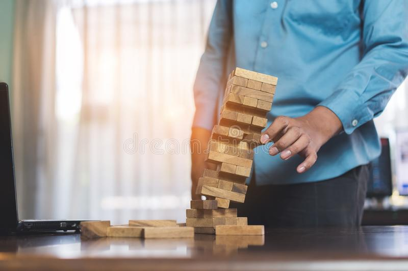 Businessman picking wooden block fail danger tower hands holding challenge game. Building construction protect plan and project for control risk shape stock images