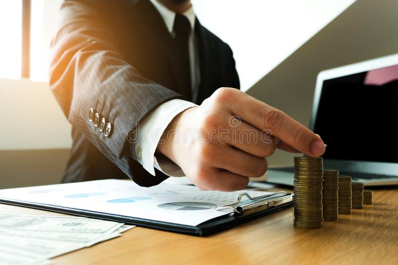 Businessman picks coins on the table, counts money . Business co royalty free stock image
