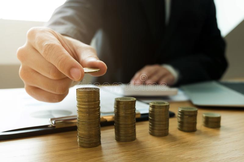 Businessman picks coins on the table, counts money . Business co stock image