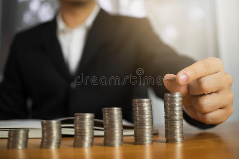Businessman picks coins on the table, counts money . Business concept stock image