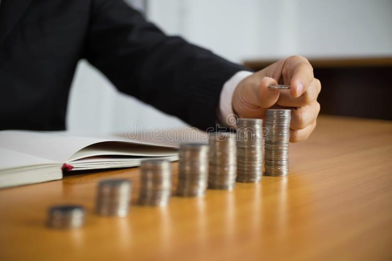Businessman picks coins on the table, counts money . Business concept stock images
