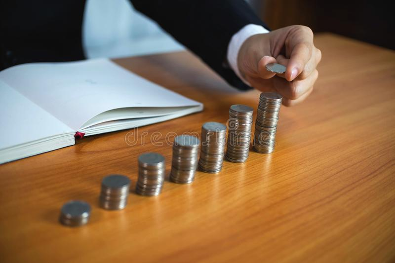 Businessman picks coins on the table, counts money . Business concept royalty free stock photos