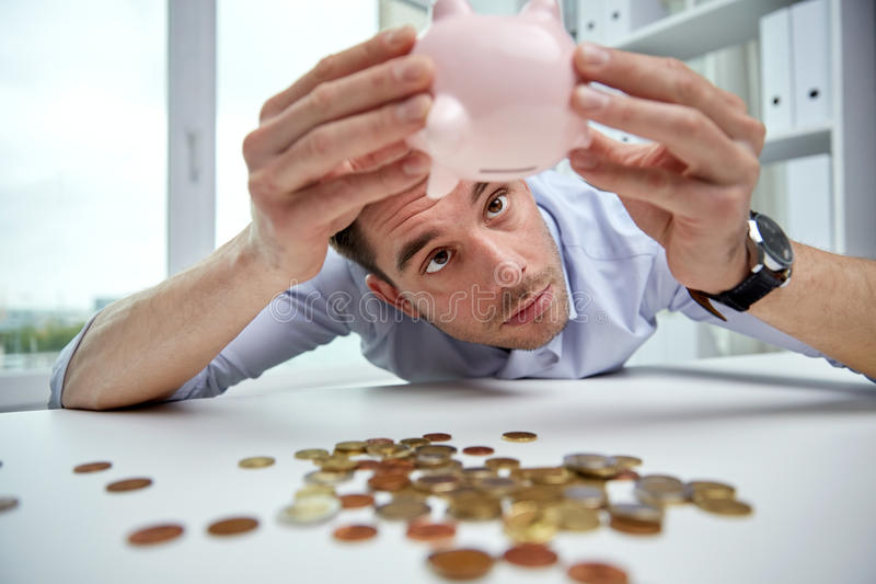 Businessman with piggy bank and coins at office. Business, people, finances, crisis and money saving concept - businessman shaking piggy bank and getting coins royalty free stock photography
