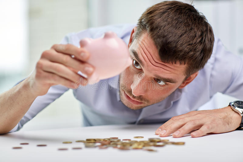 Businessman with piggy bank and coins at office. Business, people, finances, crisis and money saving concept - businessman shaking piggy bank and getting coins royalty free stock images