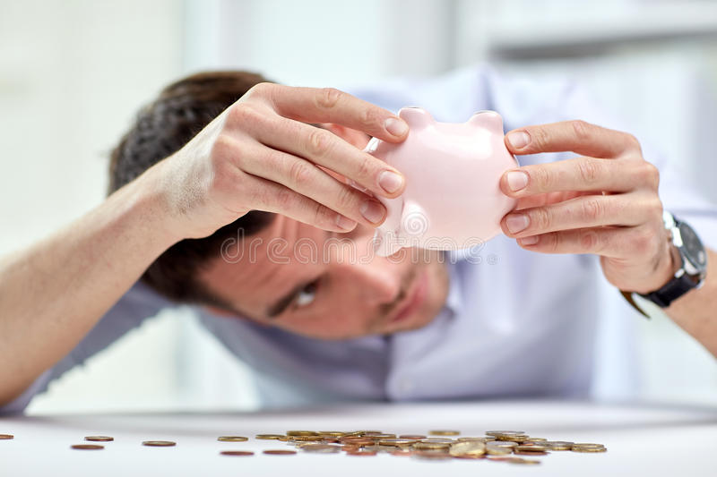 Businessman with piggy bank and coins at office. Business, people, finances, crisis and money saving concept - businessman shaking piggy bank and getting coins stock images