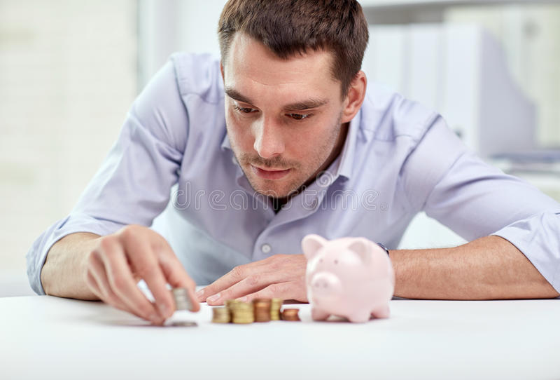Businessman with piggy bank and coins at office. Business, people, finances and money saving concept - businessman with piggy bank and coins at office stock photo