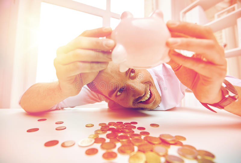 Businessman with piggy bank and coins at office. Business, people, finances and money saving concept - happy businessman shaking piggy bank and getting coins at stock image