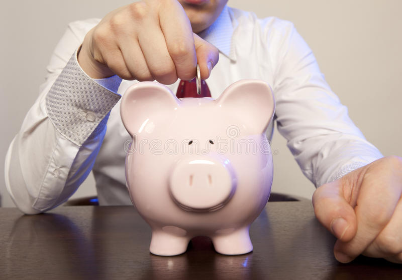 Businessman with pink piggy bank stock photography