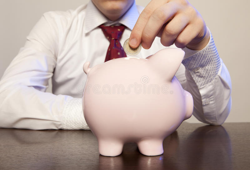 Businessman with pink piggy bank stock photo
