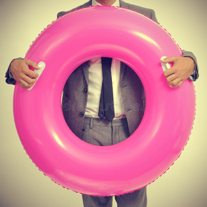 Businessman with a pink swim ring, with a retro effect royalty free stock photography