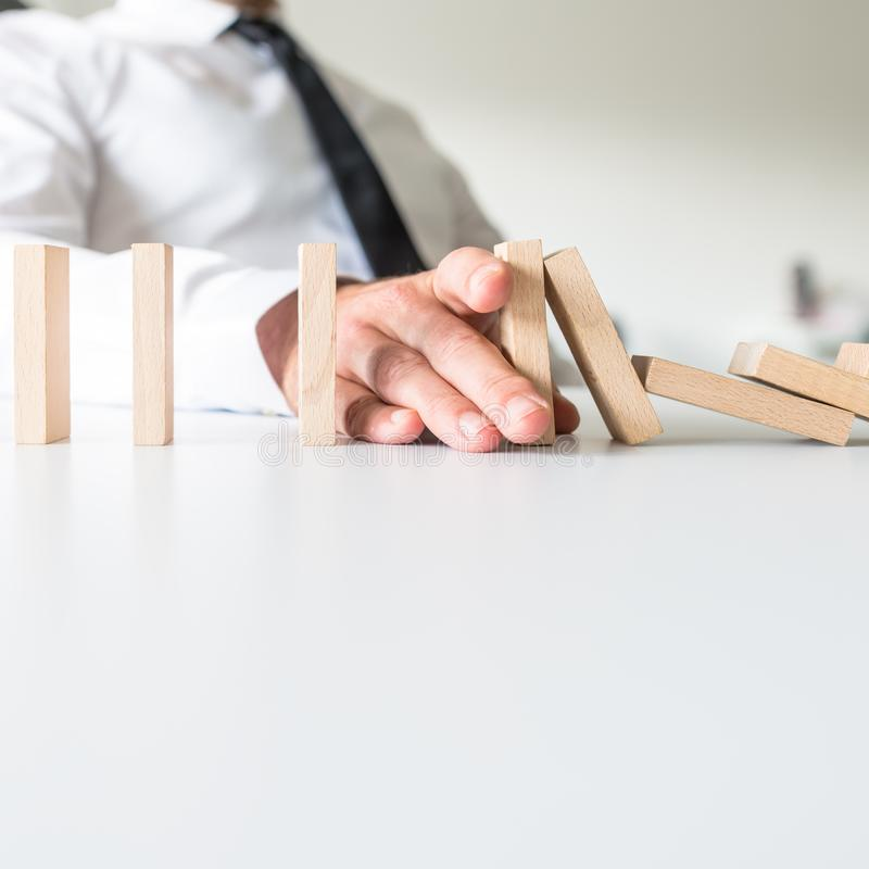 Businessman placing his hand to stop falling dominos. And prevent the crisis in a conceptual image royalty free stock photos
