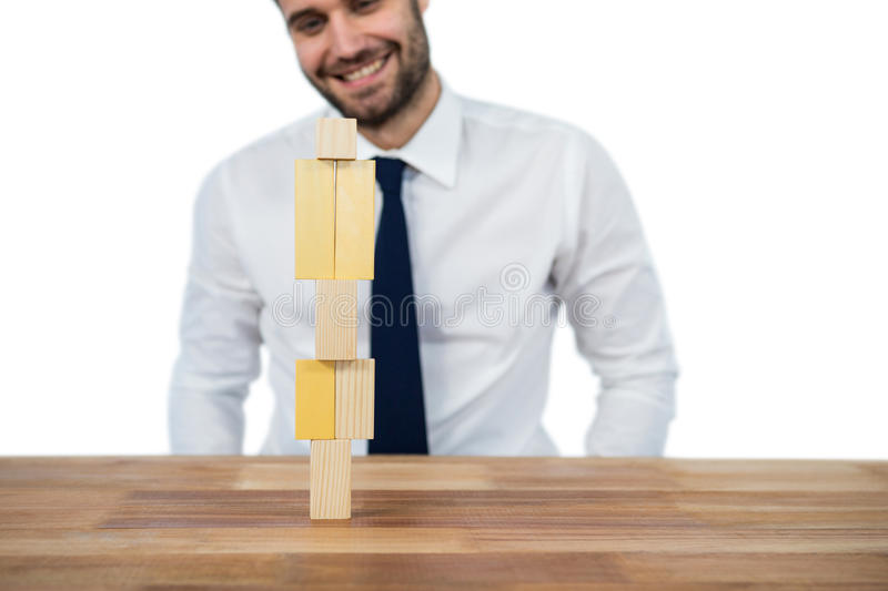 Businessman placing wooden block on a tower royalty free stock images