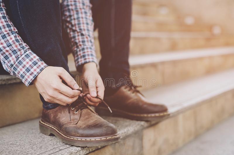 Businessman  tie up shoelace on wearing brown leather shoes sitting staircase royalty free stock photos