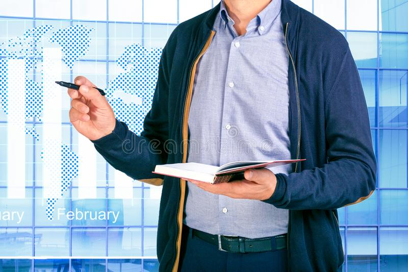 . Businessman planning business schedule with notepad and modern computer. Project management chart on virtual screen. Analysis co royalty free stock image