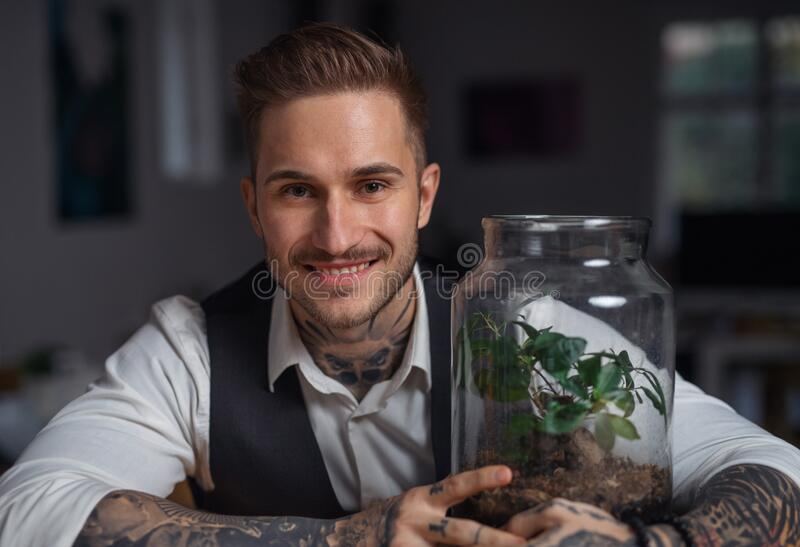 A businessman with plant terrarium sitting at the desk indoors in office. A businessman with plant terrarium sitting at the desk indoors in green office stock image