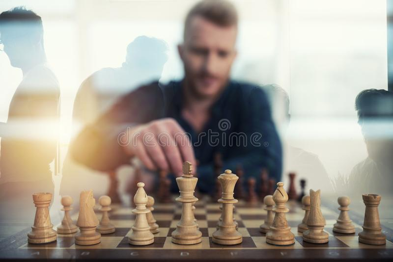 Businessman play with chess game. concept of business strategy and tactic. Double exposure. Businessman play with chess game in office. concept of business stock images