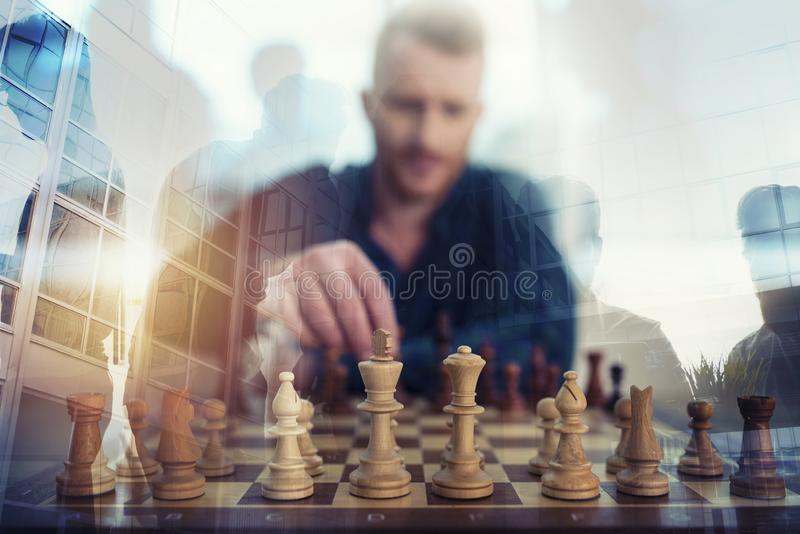 Businessman play with chess game. concept of business strategy and tactic. Double exposure. Businessman play with chess game in office. concept of business royalty free stock photos