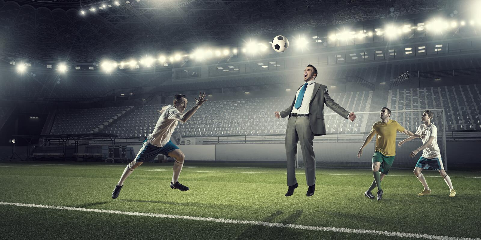 Businessman and players fighting for ball stock image