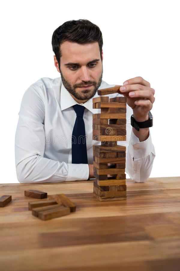 Businessman playing with building blocks royalty free stock photos