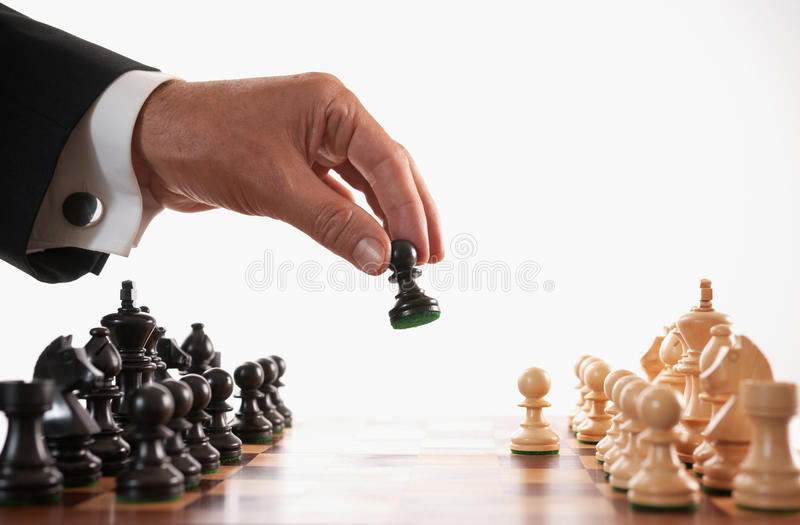 Businessman playing chess game selective focus. Back makes first move stock photos