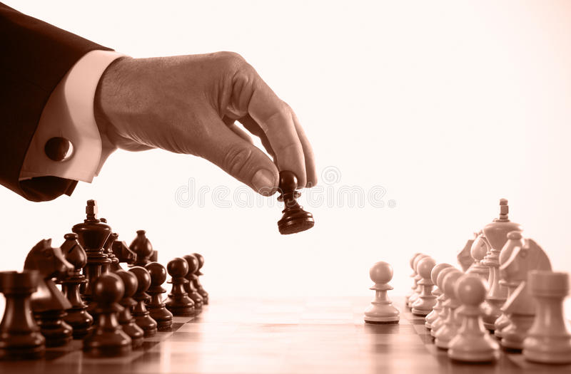 Businessman playing chess game sepia tone. Selective focus stock photography