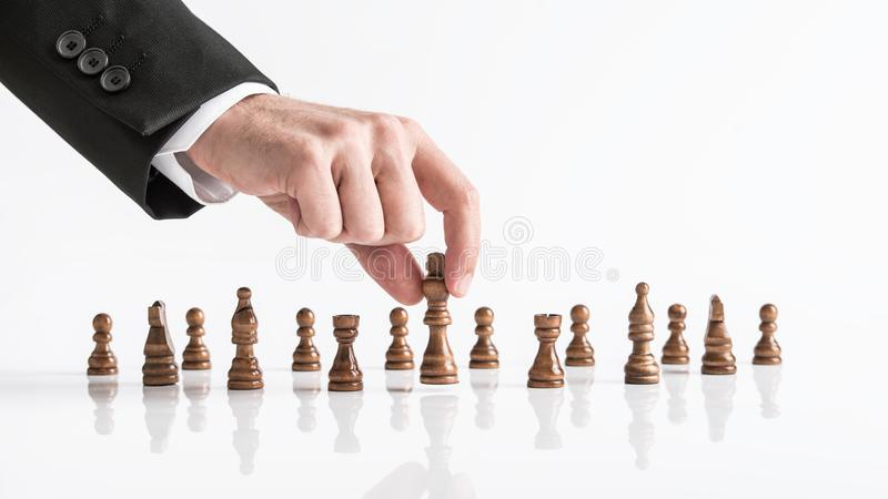 Businessman playing chess reaching dark king piece at white table. For concept about achieving goals stock photography