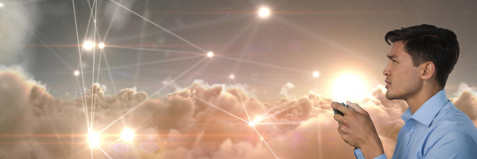 Businessman playing with computer game controller with light connections clouds background. Digital composite of Businessman playing with computer game stock photo