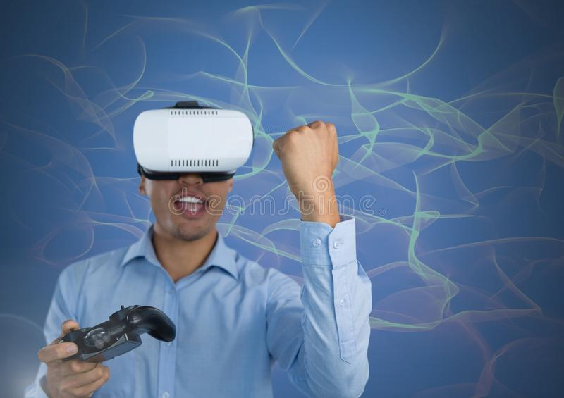 Businessman playing with computer game controller with virtual reality headset with squiggles backgr. Digital composite of Businessman playing with computer game stock images