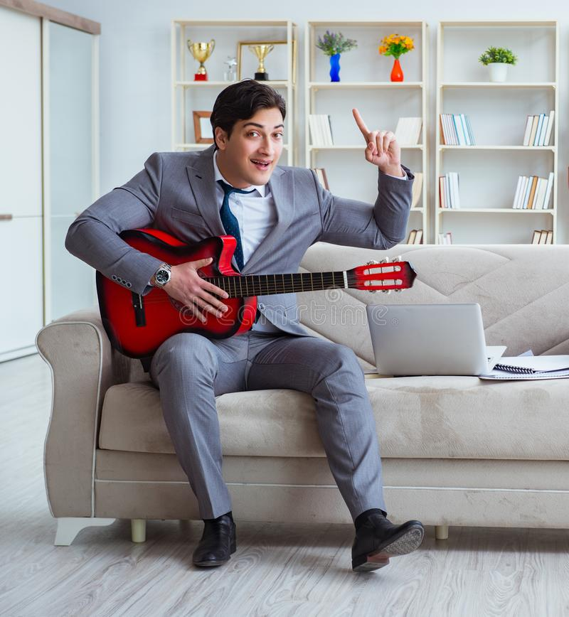 Businessman playing guitar at home. The businessman playing guitar at home stock photo