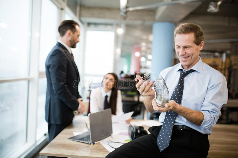A businessman is playing with a metal toy slinky. Office workers are speaking in the office behind stock photography