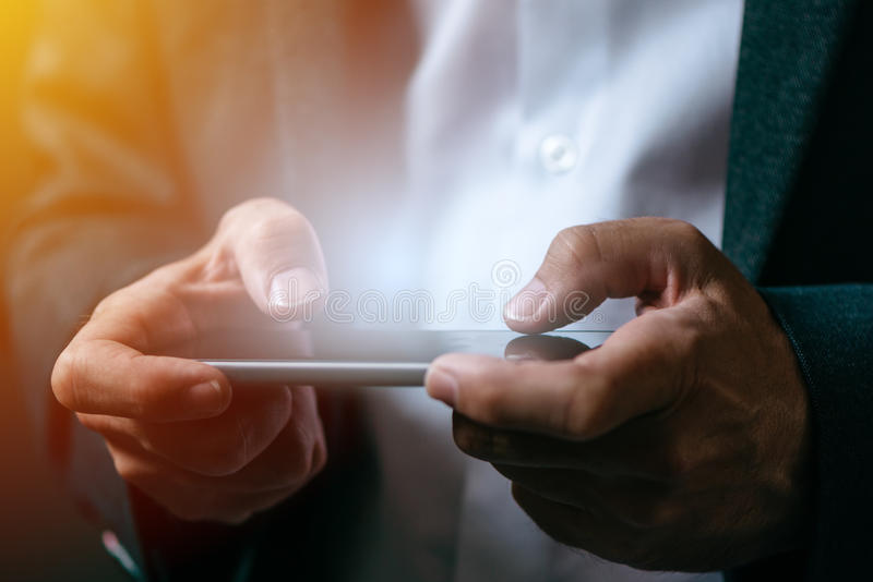 Businessman playing mobile app video game on smart phone. Close up of male hands stock photography