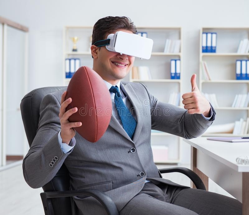 Businessman playing virtual reality football in office with VR g. Oggle stock photo