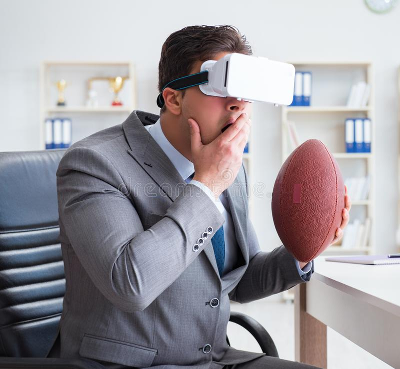 Businessman playing virtual reality football in office with VR g. Oggle royalty free stock image