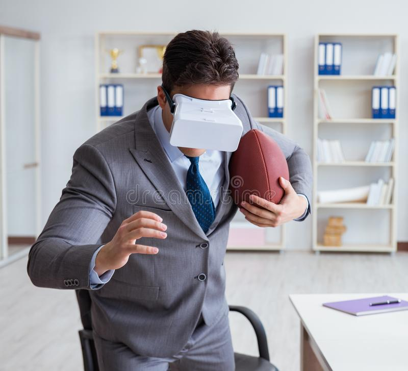 Businessman playing virtual reality football in office with VR g. Oggle royalty free stock images