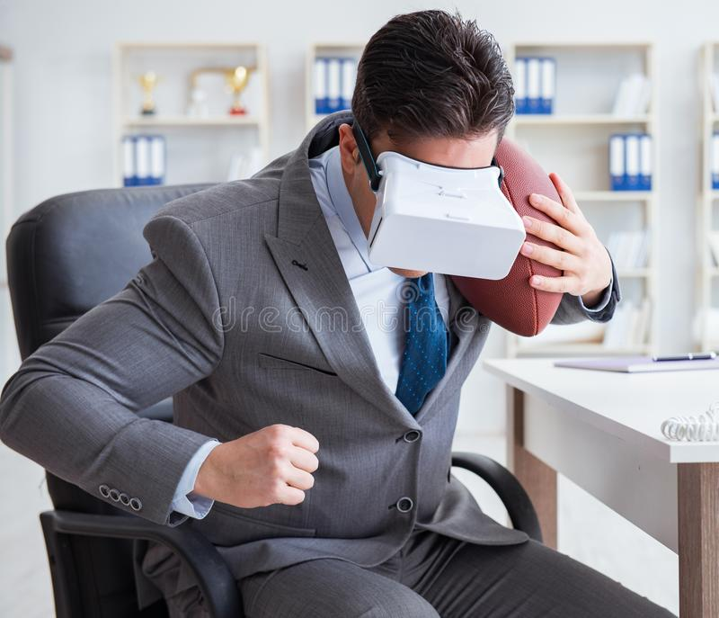 Businessman playing virtual reality football in office with VR g. Oggle royalty free stock photo