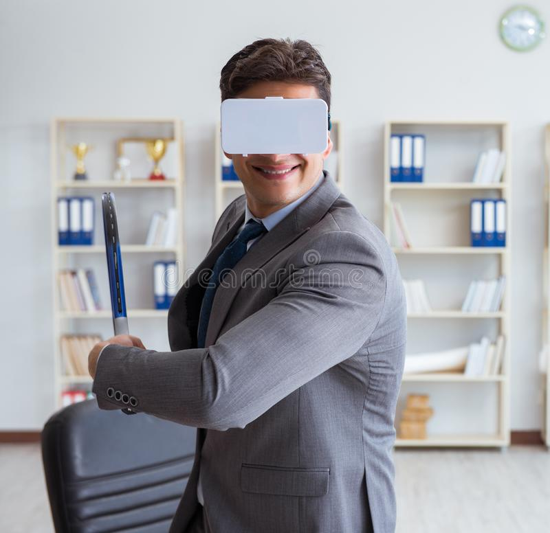 Businessman playing virtual reality tennis in office with VR gog. Gle royalty free stock photo