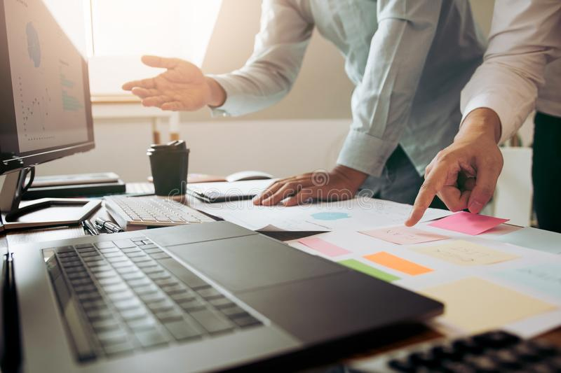Businessman point to the graph of the company financial statements in the paperwork and together analyzing the work room stock photos