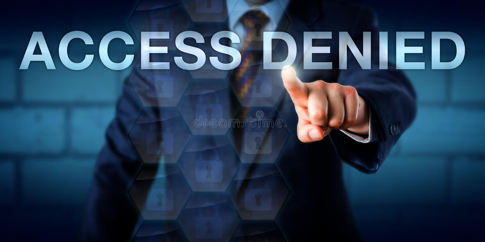 Businessman Pointing At ACCESS DENIED. Businessman is pointing at the phrase ACCESS DENIED on a virtual touch screen interface. Technology concept for secure royalty free stock images