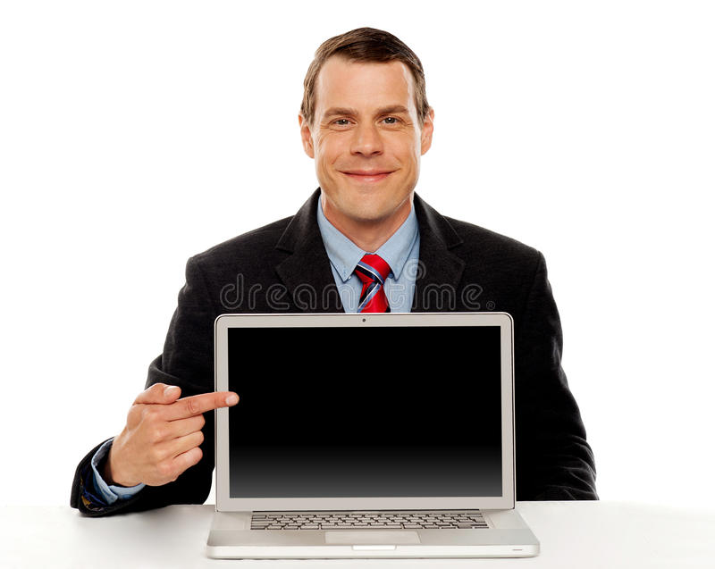 Businessman pointing at blank laptop screen stock photo
