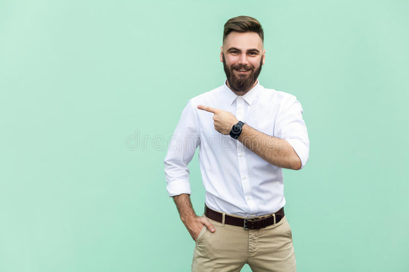 Businessman pointing copy space. Handsome young adult man with beard in white shirt looking at camera and pointing away while stan. Ding isolated on light green stock photography