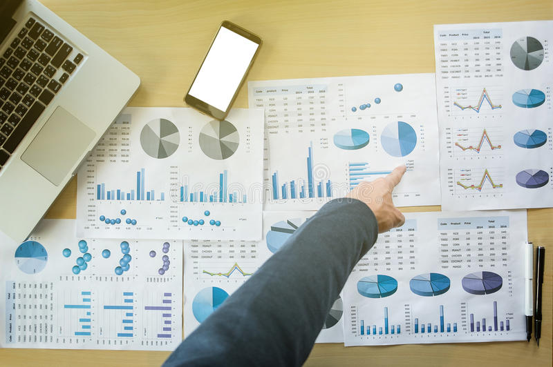 Businessman pointing documents at office working table with smart phone and computer, Top view. royalty free stock photos