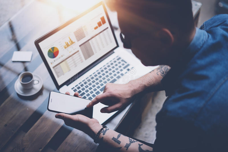 Businessman pointing finger on smartphone display.Adult tattooed coworker in eyeglasses working at sunny office on. Laptop while sitting at wooden table.Graphs stock photography