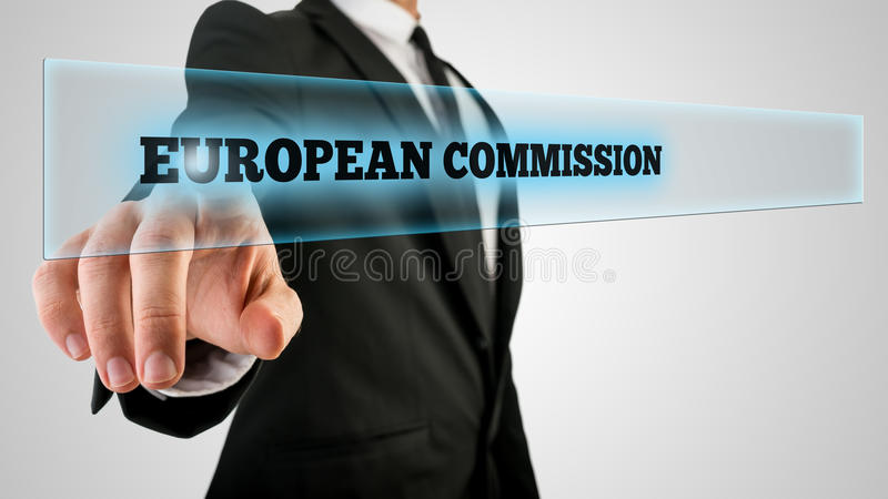 Businessman Pointing Glowing European Commission. Businessman in Black Suit Pointing Glowing European Commission Texts on Glass. Isolated on Gray Background stock photo