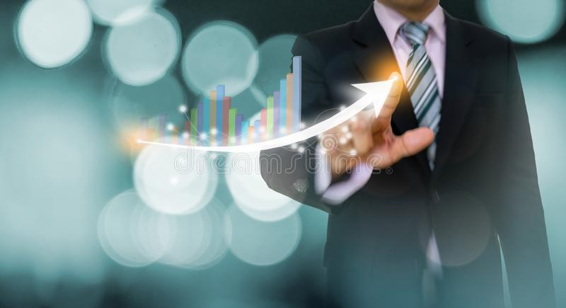 Businessman pointing graph and arrow concept development to success growing annual revenue. Growth royalty free stock photo